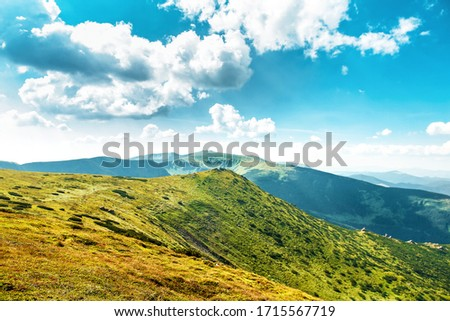 Top of summer mountains covered with green grass. Cloudy blue sky, sunny day #1715567719