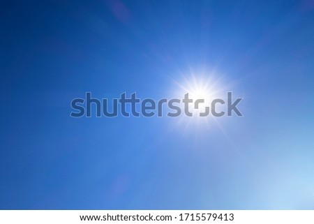 Abstract nature background of Beautiful sunny dark blue sky with bright sun shining with sunbeam, sunlight, sun rays & flares during  midday at tropical summer or spring daylight sunshine day, space   #1715579413