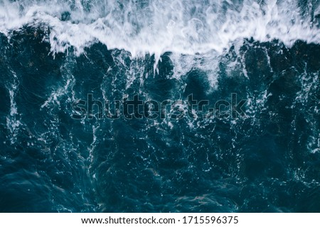 Overhead view to blue stormy ocean waves with white foam. Royalty-Free Stock Photo #1715596375
