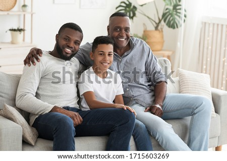 Mature Black Man Posing At Home With His Son And Grandson, Smiling At Camera, Sitting On Couch In Living Room, Bonding Together #1715603269