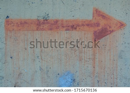 Old sign of metal rusty arrow on the fence