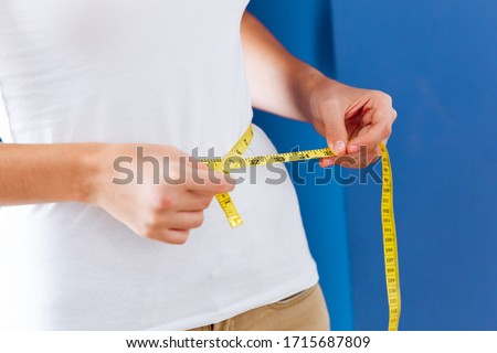 Women healthy body care weight control measuring waist fat using tape measure or measuring tape. #1715687809