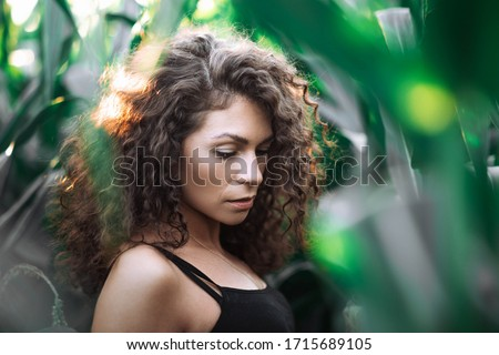 curly swarthy girl in summer corn leaves, art portrait of a woman on nature. #1715689105