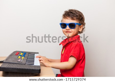 a boy in a red T-shirt and blue sunglasses plays a toy synthesizer, a piano. Learning and getting used to musical instruments from a young age.  Royalty-Free Stock Photo #1715729374