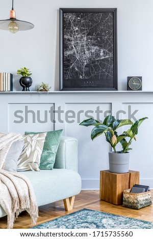 Stylish interior of living room with mock up poster frame, design sofa, wooden cube, pendant lamp, plant, carpet, pillows, plaid, books, clock and elegant personal accessories in modern home decor.