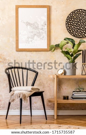Interior design of living room with stylish black chair, wooden console, books, plant, clock, decoration, grunge wall and elegant personal accessories in modern home decor.