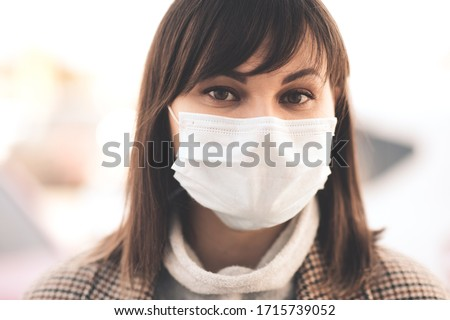 Young girl 24-26 year old wearing medical mask outdoors posing in city street. Looking at camera. Social distancing. Quarantine time. Stay home. Healthcare.  #1715739052