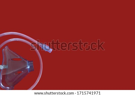 Oxygen Nebulizer Mask and Elastic cord on a red background. Flat lay  concept of Respiratory disorders. Medical stock photo. Template with copy space for text or design. #1715741971