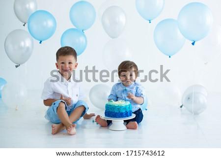 Two boys eat smash cake