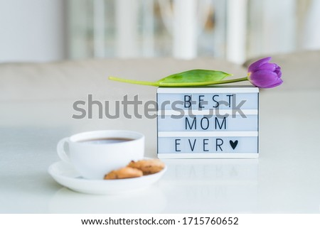Mother's day background. Morning suprise - cup of tea with cookies, lightbox with words Best mom ever and tulip flower on it standing on the marble table with light interior view. Close up. Copy space #1715760652