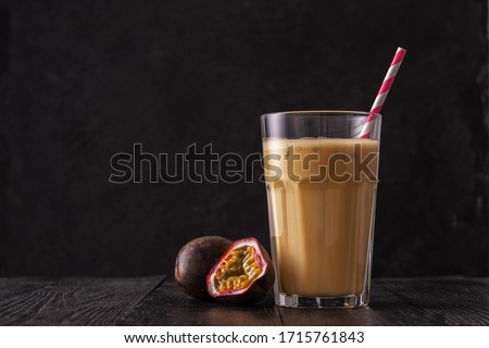 Fruit protein shake on a black wooden background. Fresh milkshake with passion fruit. A glass of protein shake. #1715761843