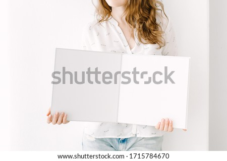 Woman stands with an open empty book. White book mockup. Opened square empty book. Album with a clean pages in hands. Clean book mock up. Mock-up is ready to design. Young woman with an album template #1715784670