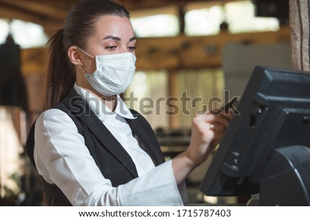 work of a waiter in a restaurant in a medical mask Royalty-Free Stock Photo #1715787403