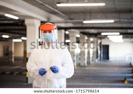 Coronavirus COVID-19 virus disease pandemic outbreak,UK NHS EMS key medical worker in Personal Protective Equipment,US hospital parking drive-thru rt-PCR test lot,Intensive Care Unit first responder #1715798614