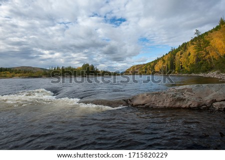 Autumn on the wild forest river. Wild nature landscape. Fishing in far est. Stones on the shore of taiga river #1715820229