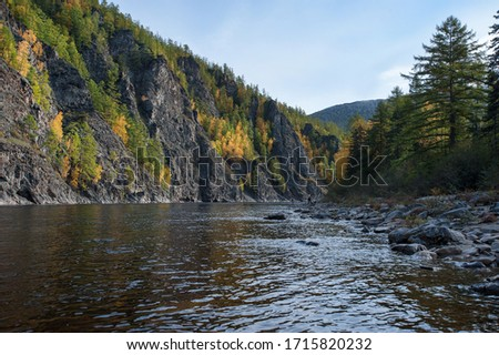 Autumn on the wild forest river. Wild nature landscape. Fishing in far est. Stones on the shore of taiga river #1715820232