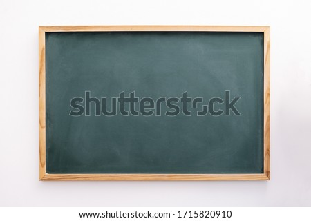 blank green chalkboard on a white wall, school and teaching concept, copy space for text #1715820910