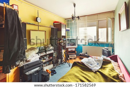 Messy room interior, a lot of different stuff, from electronic appliances and furniture to clothes.  Royalty-Free Stock Photo #171582569