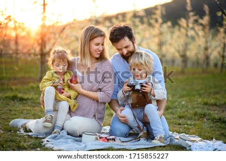 Family with two small children having picnic outdoors in spring nature at sunset. #1715855227