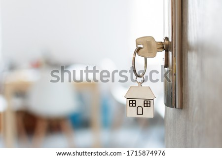 Key with keychain in a house shape in the door keyhole. Buy new home concept. Real estate market. #1715874976