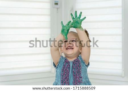 Little girl paints with fingers.girl joyfully raised her hands in raska up, self-isolation, coronavirus covid-19, stay home #1715888509