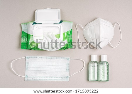 White medical masks and respirators with antibacterial wet wipes, disinfectant spray and hand sanitizer. Personal hygiene product for protection virus, flu, coronavirus, COVID-19 #1715893222