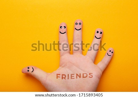 Hand with fingers smiles isolated on yellow background, concept of friendship. #1715893405