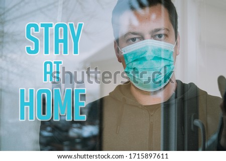man in isolation looking trough window with mask and gloves in isolation protecting from coronavirus covid-19 with text stay at home #1715897611