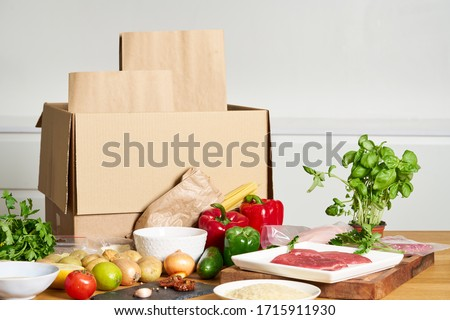 Box with packed meat vegetables on kitchen background. Food delivery services during coronavirus pandemic and social distancing. Shopping online. Dinner delivery service. Royalty-Free Stock Photo #1715911930