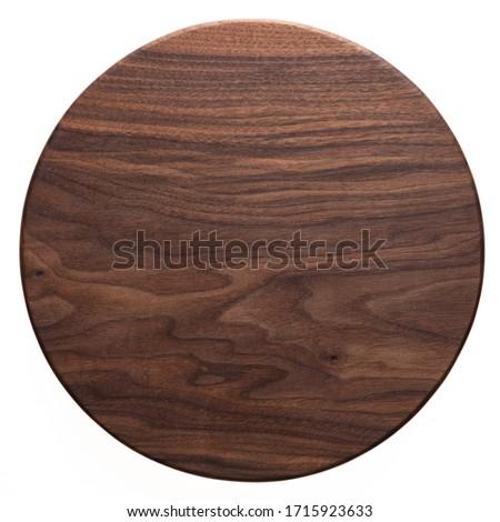 Handmade black walnut round wood plate. Walnut round wooden tray. Black walnut wood plank texture background. Royalty-Free Stock Photo #1715923633