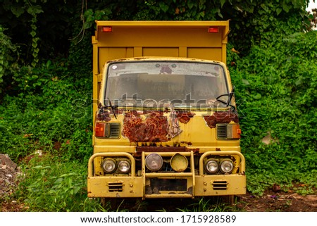 An Indonesian dump truck abandoned in the jungle. Car on the background of a green forest. Rusty cab of the vehicle. Large pockets of rust. A car with a towbar. #1715928589