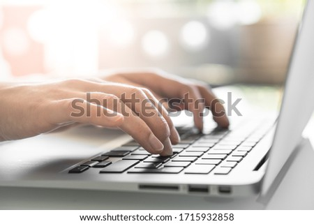 Hands writing ond a keyboard of a laptop or a notebook in Home Office #1715932858