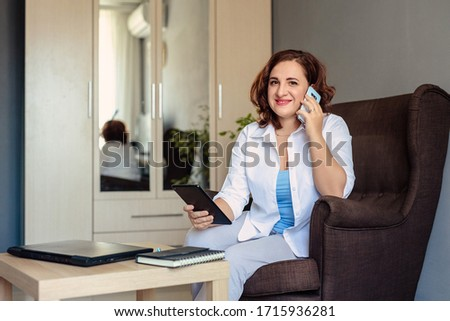 young beautiful woman 30 years old in a white shirt works, sitting in a chair in the home office and discusses problems with the customer using video calling #1715936281