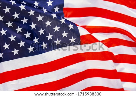 Fabric texture flag of USA. Flag of United States of America waving in the wind. US flag is depicted on a sports cloth fabric with many folds. Sport team banner. #1715938300