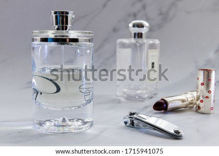 Perfumes in bottles, nail clipper and lipstick. Women beauty and care products set in a grey marble background. #1715941075