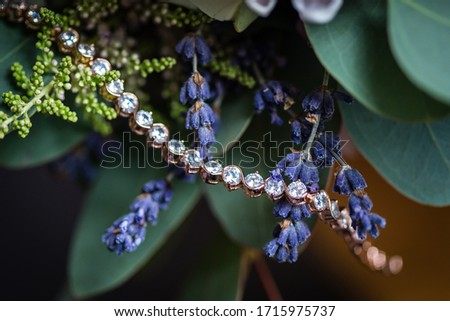 Close up picture of the shining golden crystal clear gemstone bracelet hanging on the violet lavender branch,  greens on the background