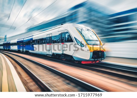 High speed train in motion on the railway station at sunset. Modern intercity passenger train with motion blur effect on the railway platform. Industrial. Railroad in Europe. Commercial transportation #1715977969