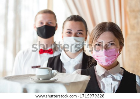 work of a waiter in a restaurant in a medical mask #1715979328