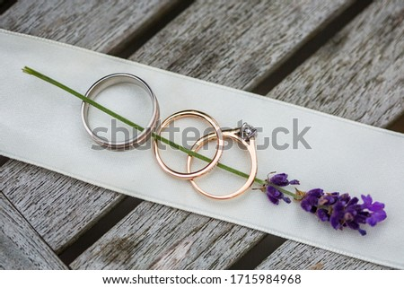 Close up picture of the golden wedding rings and engagement ring with round diamond, placed on the violet lavender brunch, cream ribbon and grey wooden table on the background