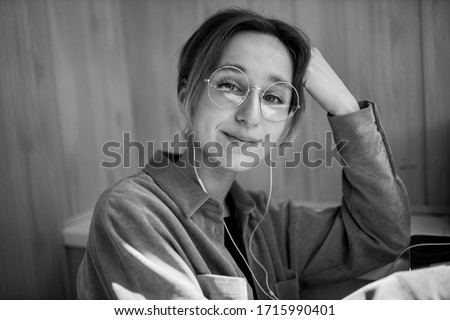 European girl using a mobile phone communicates with friends in an online chat. a smiling girl with glasses communicates in an online chat via video communication. black and white photo