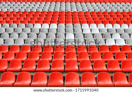 Empty seats in the stands of the arena or auditorium. Rows of red and white stadium seats without spectators. The concept of the abolition of sports and mass entertainment events Royalty-Free Stock Photo #1715991040