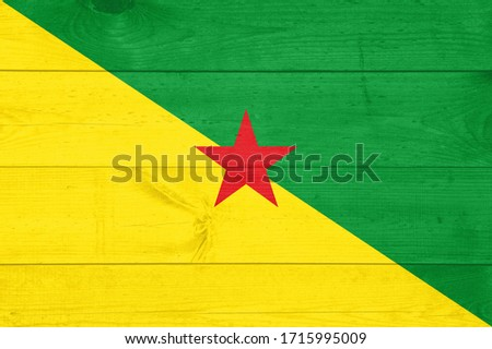 French Guiana national flag painted on old oak wood. Painting is colorful on planks of old train carriage. #1715995009