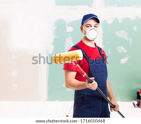 Portrait of a masked painter at work in an apartment, renovation and home painting during coronavirus pandemic #1716010468