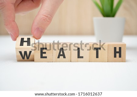 Concept health wealth on wooden block hold hand. Close up. Royalty-Free Stock Photo #1716012637