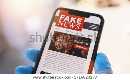 Online Corona Fake news on a mobile phone. Close up, man reading Fake news or articles about covid-19 in a smartphone screen application. Hand with gloves holding smart device. COVID19 nCov Outbreak. #1716020299