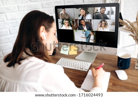 Online training. The back view of a girl who learns online by video conference online. On the screen, the teacher tells the information to her and other participants in the conference #1716024493