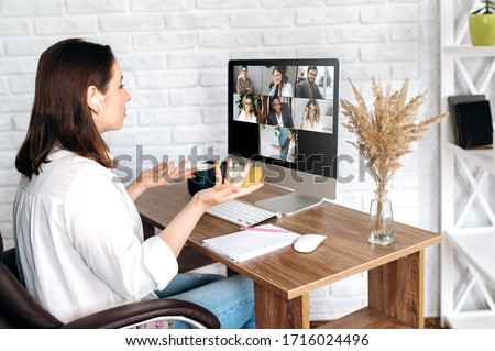 Video call. Remote work. A girl work from home. She communicate via video communication with colleagues using computer #1716024496