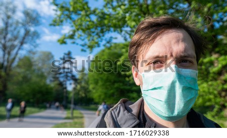 portrait of young European man wearing medical face mark enjoying outdoor activities green park background. During New Corona virus (Covid-19) pandemic. #1716029338
