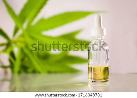 Glass bottle with cbd oil on white background with marihuana leaf Royalty-Free Stock Photo #1716048781