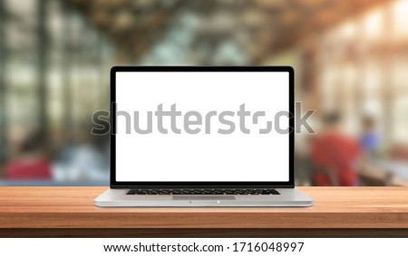 Laptop or notebook with blank screen on wood table in blurry background with coffee shop and nature green bokeh and sun light in morning.